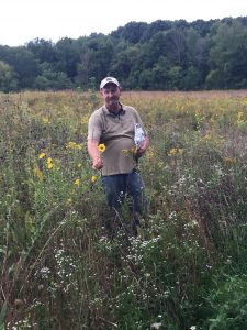 Prairie restoration project leader Mike Bruggink points out a Maximillian sunflower